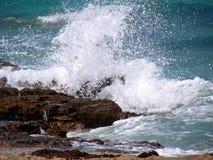 Wave hitting rocks Stock Photos
