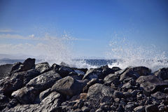 Wave hitting rocks with blue sky Stock Image