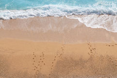 Wave hitting  the Shoreline. Footsteps on the beach blue sea Royalty Free Stock Photo