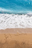 Wave hitting  the Shoreline Vertical. Wave hitting  the Shoreline footsteps on the beach blue sea Stock Images