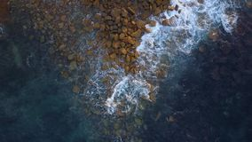 Wave hitting triangular rocks stock footage