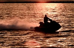 Wave jet in sunset. Single seated personal watercraft skips along the water creating a trail of water. Setting sun creates a warm color on the rippling water royalty free stock image