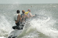 Wave Jumper. A three person wave runner in the ocean. A family riding a water sport vehicle in the ocean waves stock image