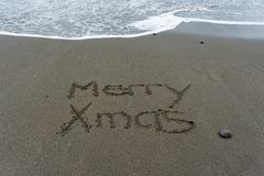 Merry Xmas hand written in the sand with the sea in the backgrou stock images