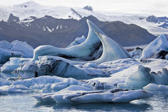 Wave-like icebergs in Jokulsarlon. Fantastically shaped icebergs floating in lagoon before snow-capped mountain and glacier royalty free stock photo