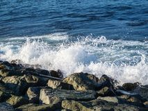 Wave meets breakwater stones royalty free stock photos