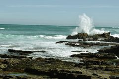 Wave meets rock. A wave from the incoming tide meets a rock and the inevitable happens at Agulhas SA Stock Photography