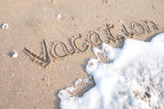 Wave is moving to word Vacation on sand Royalty Free Stock Photos