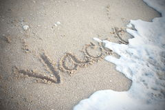 Wave is moving to word Vacation on sand Royalty Free Stock Photo