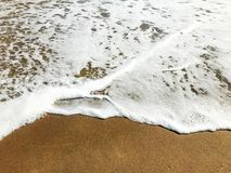 Wave nibble on sand beach. Sand clean beach background with sea wave on the top. Wave nibble on sand Sri Lanka beach. Sand clean beach background with sea wave royalty free stock photo