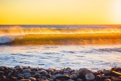 Wave in ocean at colorful sunset or sunrise. Crystal wave on sea. Wave in ocean at colorful sunset or sunrise. Crystal wave Stock Photo