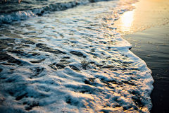 Wave of the ocean sea on the sand beach at the sunset light. Close up view Stock Photography