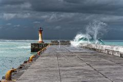 Wave over pier during storm, in Cape Town South Africa royalty free stock photo