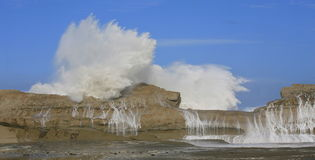 Wave over rock. Large wave crashing over natural rock cliff face, near Castle Rock New Zealand Stock Photography