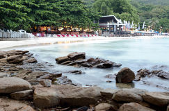 Wave over rocks with bar and restaurant on the beach. In Thailand Stock Photography