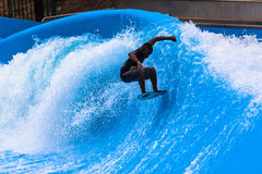 Wave Pool Action Surfer. Wave pool surfer doing action tricks in the  fast standing wave for the next competition.Photo image looking down on the athlete Royalty Free Stock Photography