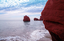 Wave on red cliffs at Dune de Sud Royalty Free Stock Photography