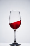 Wave of red wine in a crystal pure wineglass standing against light background with reflection. Royalty Free Stock Image