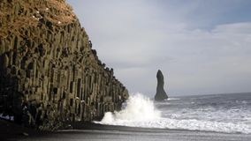 Wave on Reynisdranger, Iceland. Reynisdranger, basalt sea stacks with the wave and black sand beach near the small village Vik i Myrdal in the south of Iceland stock footage