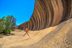 Wave Rock jumper. Australian outback freedom concept. Happy Caucasian woman jumping at Wave Rock in Hyden, Western Australia. Female jumper in a natural rock royalty free stock photography
