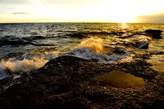 Wave on the rock at sunset Stock Photography