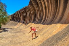 Wave Rock surfing. Young woman enjoying surfing on the Wave Rock, a natural rock formation that is shaped like a tall breaking ocean wave, in Hyden, Western Stock Photography