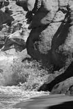 Wave on rocks. Wave hitting beach rocks, monochrome Royalty Free Stock Images