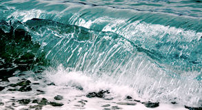 Wave rolling on the pebbels beach. Sea wave rolling on to the shore, evening shot. closeup Royalty Free Stock Photos
