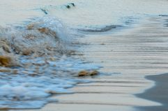 Wave rolling at seaside over brown beach sand. In the morning Royalty Free Stock Photos