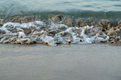 Wave rolling at seaside over brown beach sand. In the moring Stock Image