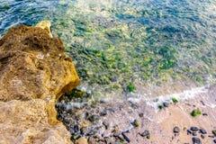 Wave rolls onto the rocks of sandy coast Royalty Free Stock Photo
