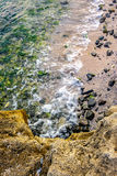 Wave rolls onto the rocks of sandy coast Royalty Free Stock Photos