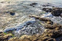 Wave rolls onto the rocks of sandy coast Royalty Free Stock Image