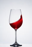 Wave of the romantic drink red wine on the pure wineglass standing against light background with reflection. Royalty Free Stock Photography