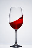 Wave of the romantic drink red wine on the pure wineglass standing against light background with reflection. Royalty Free Stock Images