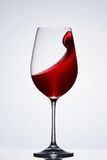 Wave of the romantic drink red wine on the pure wineglass standing against light background with reflection. Stock Photography