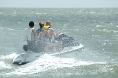 Wave Runner. A three person wave runner in the ocean. A family riding a water sport vehicle in the ocean waves royalty free stock photos