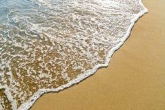 Wave running on the sand. Foamy wave gliding towards the golden beach Stock Photos