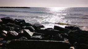 Wave on the sand beach - stones shore. In the sunlight stock video footage
