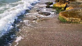 Wave on the sand beach - stones shore. And wave that broke at the shore in the sunlight stock video