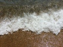 Wave on sand 1. Closeup of a wave in the sea. The water and foam are flowing over the sand. With space for text Royalty Free Stock Images
