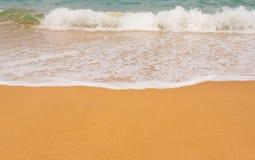 Wave on a sandy beach royalty free stock photos