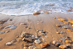 Wave of the sea on the beach  with sand and stones Stock Photos