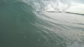 Wave in the sea. Camera moves along the wave barreling and breaking in the sea stock video