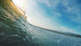 Wave in the sea. Camera moves along the wave barreling and breaking in the sea stock footage