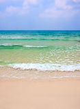 Wave of the sea on the sand beach against clody sk Royalty Free Stock Photos