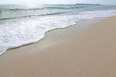 Wave of the sea on the sand beach background, Sea foam Royalty Free Stock Image