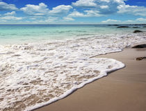 Wave of the sea on the sand beach and blue sky Stock Photo