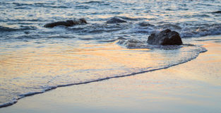 Wave of the sea on the sand beach. Seashore on sunset Royalty Free Stock Photo