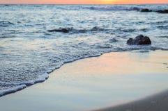 Wave of the sea on the sand beach. Seashore on sunset Stock Photography